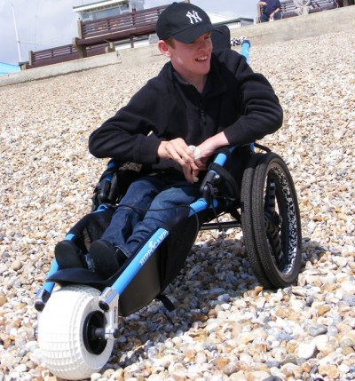 Sitting in a Hippocampe Beach Wheelchair on a pebbly beach
