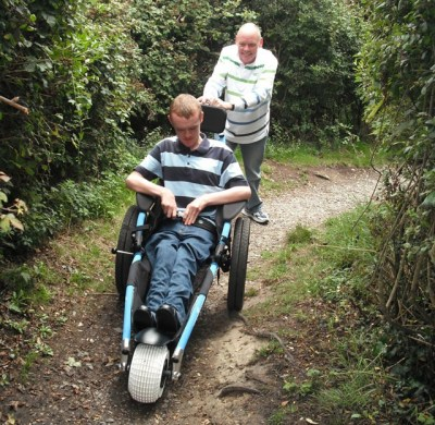 Hippocampe all-terrain wheelchair being pushed along a woodland path